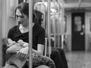 mom breastfeeding on subway